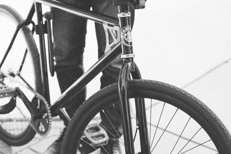 A close up of a man walking with bike